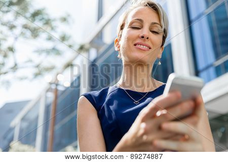 Businesswoman with a phone in a city