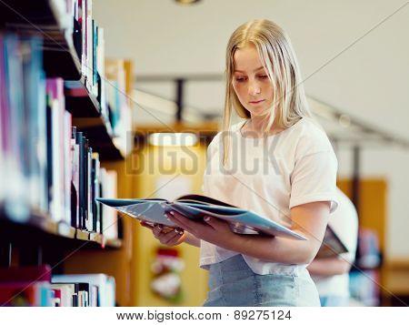 teenage girl in library choosing books