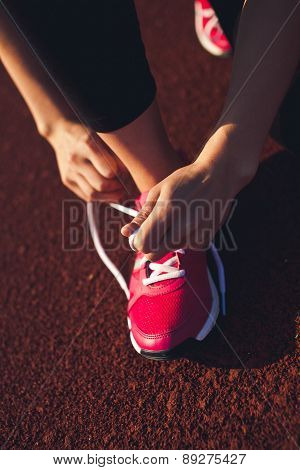 Girl ties laces on running shoes