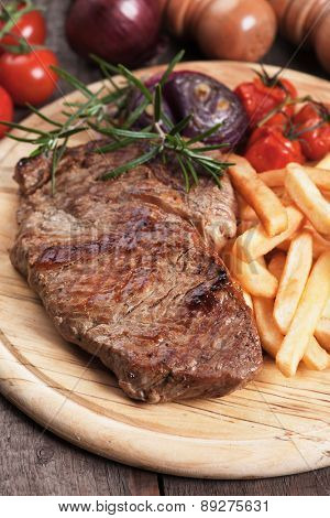Beef rib-eye steak with french fries on wooden board