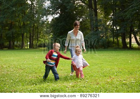 happy family playing together outdoor  in park mother with kids  running on grass