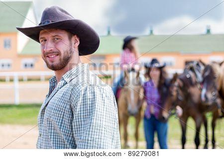 cowboy closeup portrait on background of horses