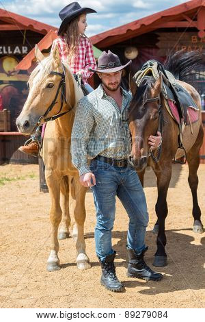 cowboy father and daughter with horses