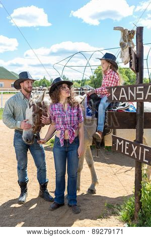 cowboy family of three looking at a scull on signpost