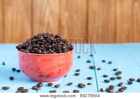 Coffee beans in red bowl on blue table and dark wooden background