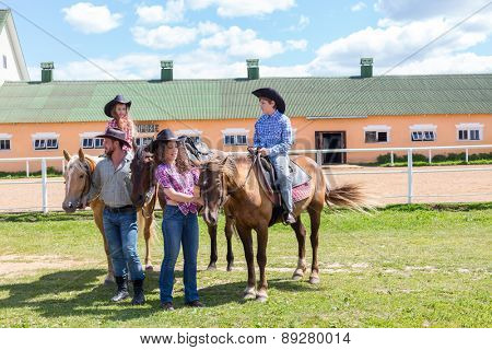 cowboy family of four with horses on grass