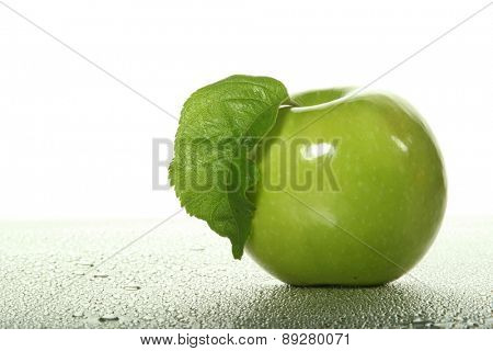 Green apple on wet background