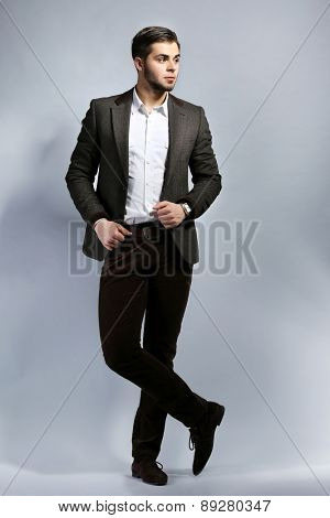 Elegant man in suit on gray background