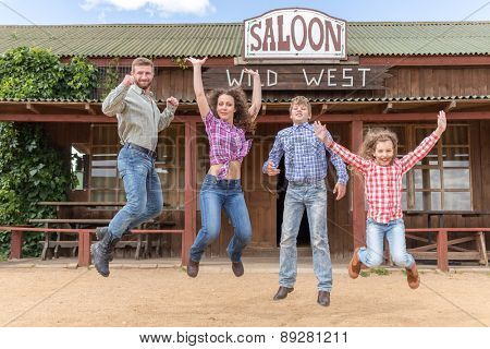 family of four jumping on background of  wild west saloon