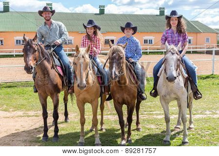 cowboy family of four on horses on background of paddock