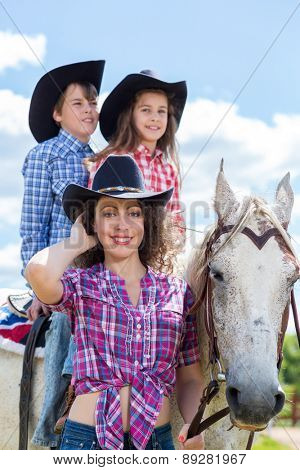 cowboy mother with son and daughter on a horse