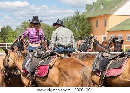 cowboy couple sit back stroking horses