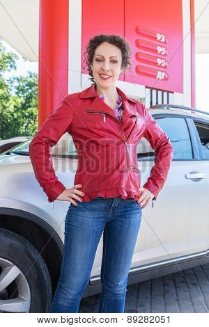woman posing on background of a car on gasoline station
