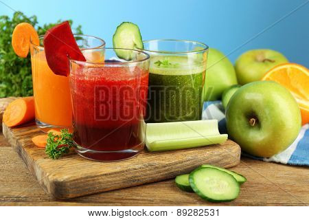 Assortment of healthy fresh juices in glass bottles on wooden table, on blue background