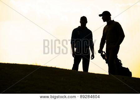 Silhouette of young men standing in golf course with trolley