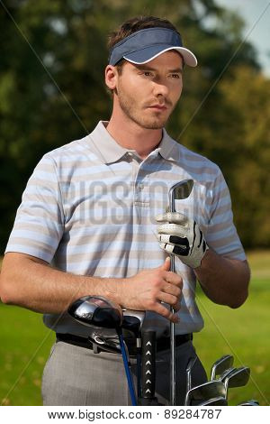 Young man standing by golf bag full of sticks