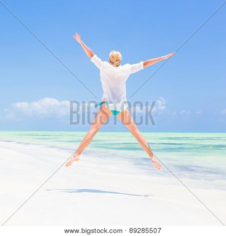 Beautiful Girl Jumping on Tropical Beach.