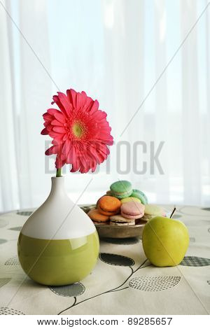 Color gerbera flower in vase and apple with macaroons on table on curtains background