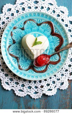 Tasty panna cotta dessert on plate, on wooden table