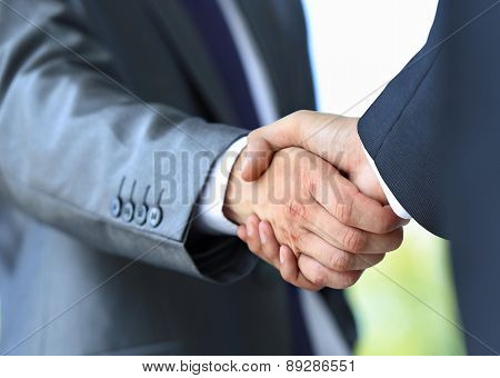 Close-up of business people handshaking on bright background
