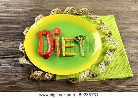 Word DIET made of sliced vegetables in color plate on wooden table, closeup