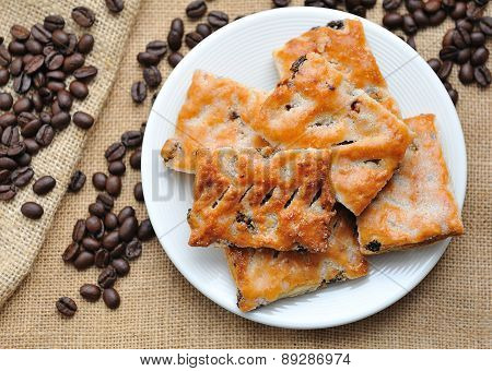 Cookies in plate  with coffee beans on canvas.