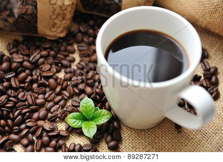 Cup of coffee with beans and leaf