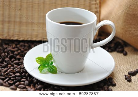 Close up of coffee and  coffee beans with leaf on texture background, selective focus.