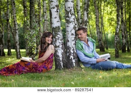 Young couple holding books in park by tree trunk, looking at each other