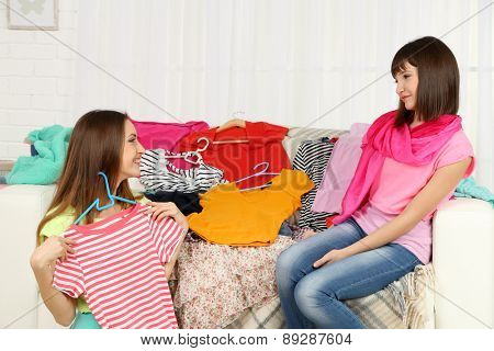 Two girls selecting and trying clothes at home