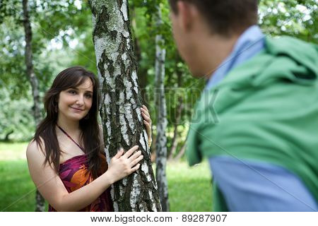 Young couple standing in park by tree trunk