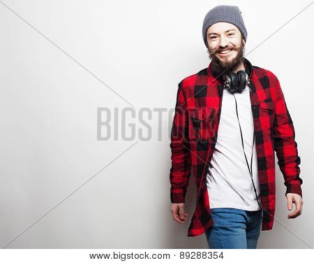 emotional and people concept: young bearded man wearing hat with headphones