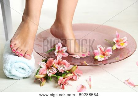Woman washing beautiful legs in bowl, on light background. Spa procedure concept