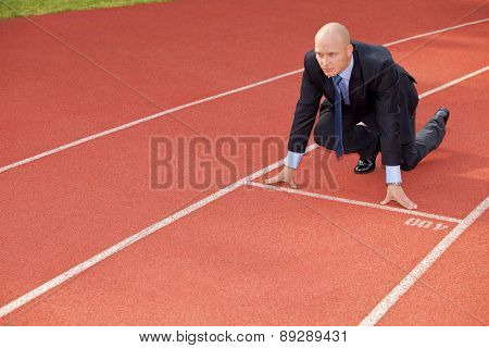 Businessman at the start line of running track