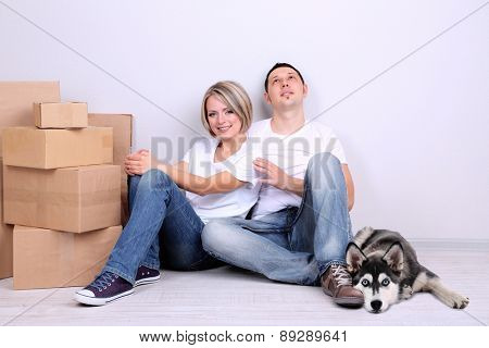 Young couple with husky dog moving in new house