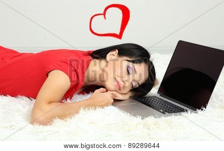 Beautiful young woman asleep at notebook in room