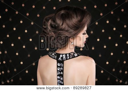 Elegant Brunette Woman With Hairstyle. Fashion Glamour Lady With Gemstone On Back Posing Against The