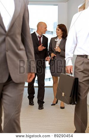 Business team walking thru corridor and talking