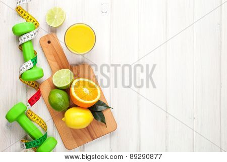 Citrus fruits, tape measure and dumbells. Oranges, limes and lemons. Healthy food. Over wood table background with copy space