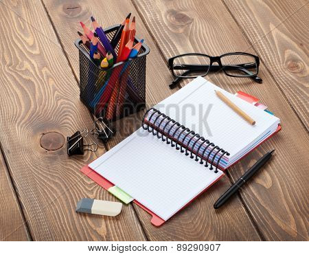 Office table with blank notepad and supplies. With copy space
