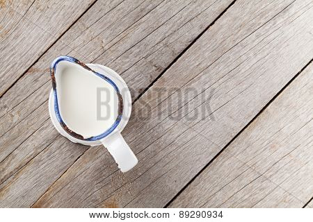 Milk jug on wooden table. View from above with copy space