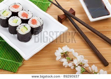 Sushi maki set and sakura branch on bamboo table