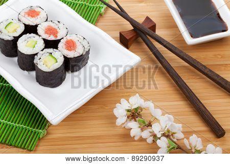 Sushi maki set and sakura branch on bamboo table