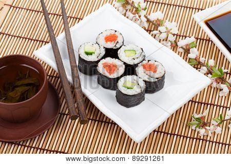 Sushi maki set, green tea and sakura branch over bamboo table