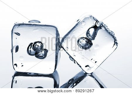 Two melting ice cubes with water dew on white background