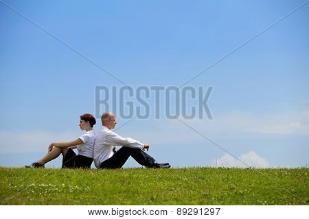 Business couple sitting back to back on grass