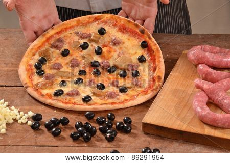 Cook holding olive baked pizza.