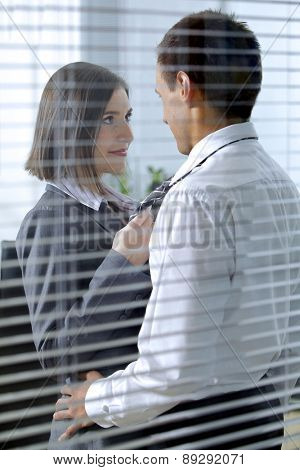 Businessman and woman standing in office, looking at each other