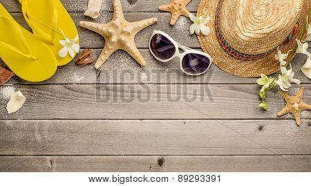 Straw hat,sunglasses and beach slippers on wood