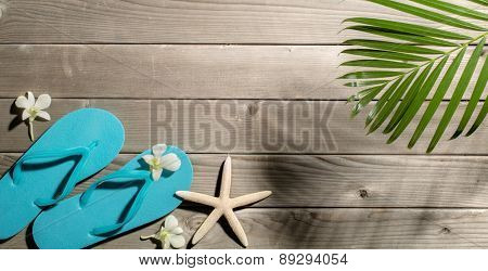 Beach slippers,starfish and palm leaf on wood background